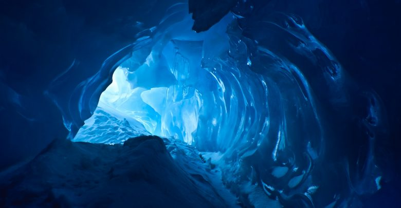 An image of a Blue Ice Cave with background light. Shutterstock.
