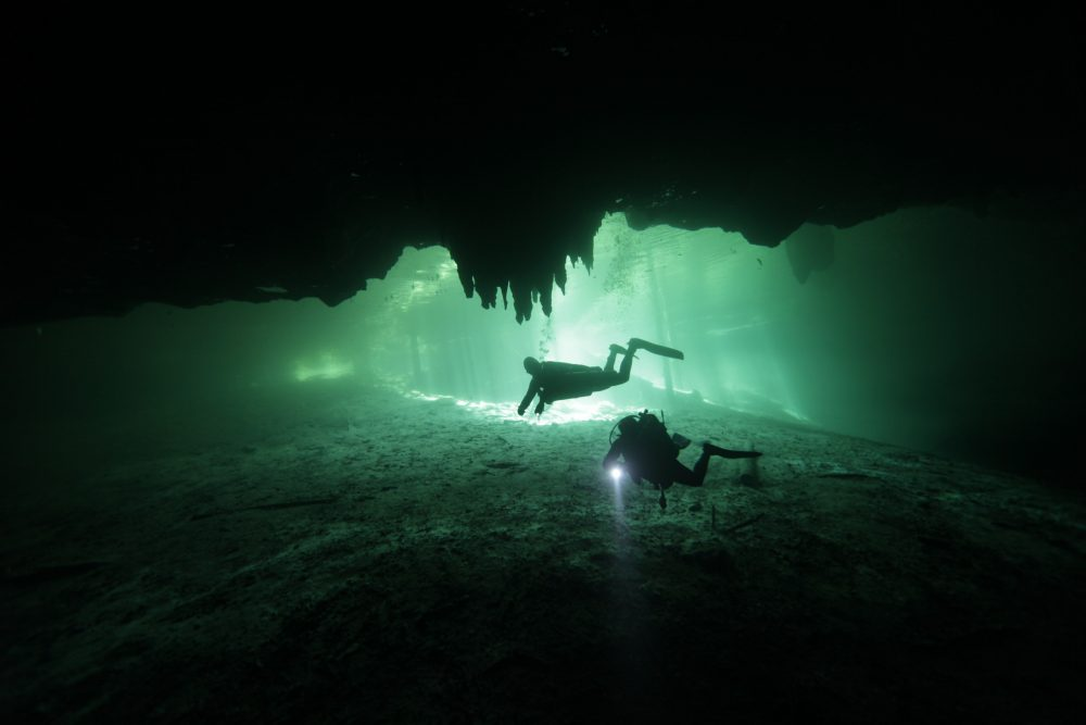 An image of Divers in the cenote Dreams Gate at Playa del Carmen in Mexico. Shutterstock.