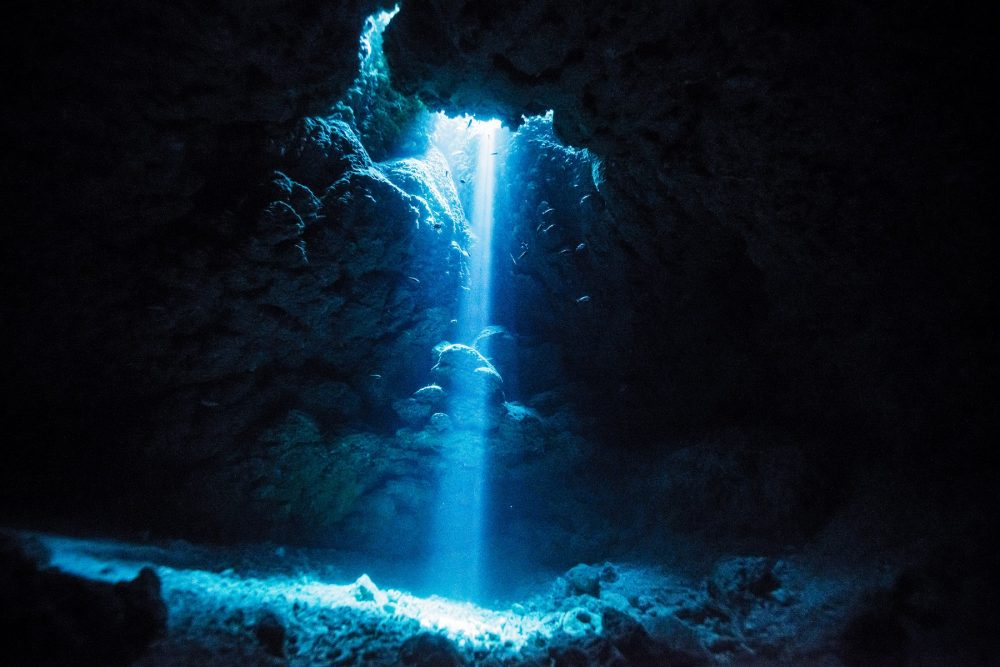 An image of sunlight rays entering a sunken cave. Shutterstock.