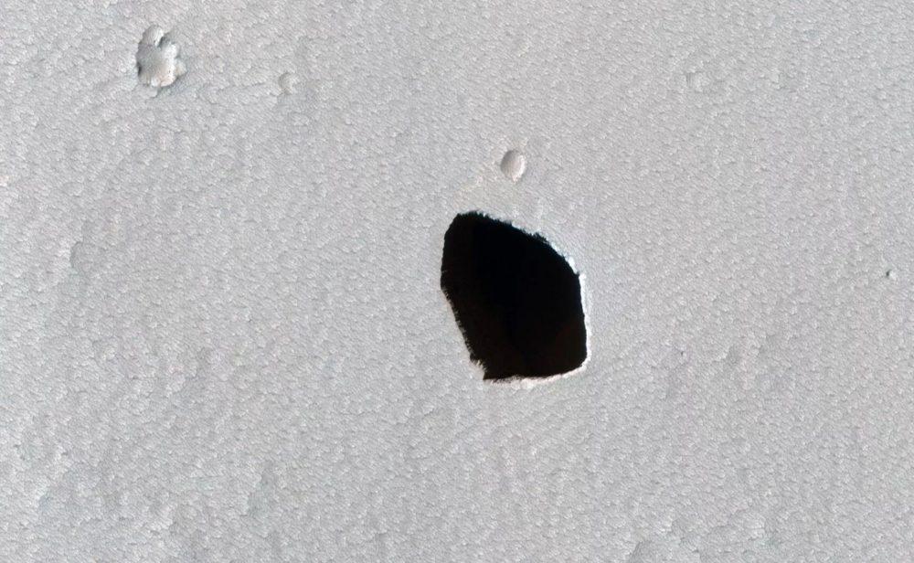 An image of a dark pit on the surface of Mars. Image Credit: NASA/JPL/University of Arizona.