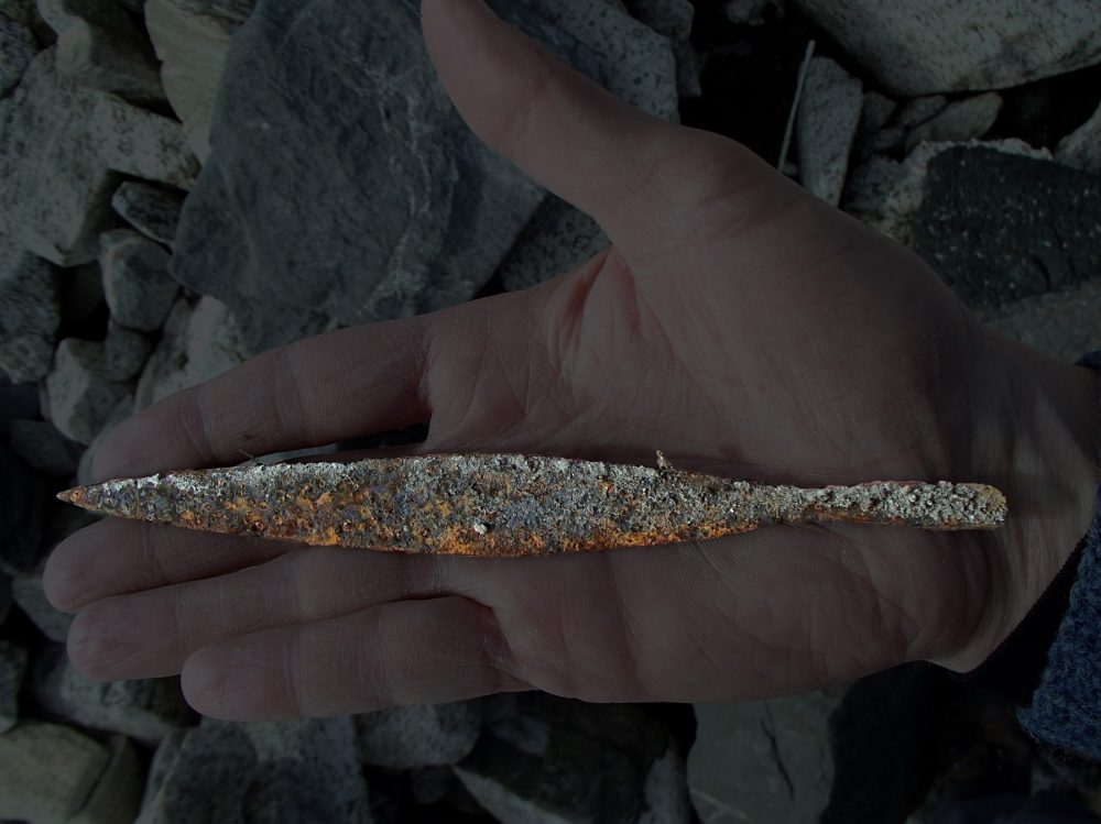An image of the ancient Viking arrowhead being held by an archeologists in Norway. Image Credit: Secrets of the ice / Twitter.