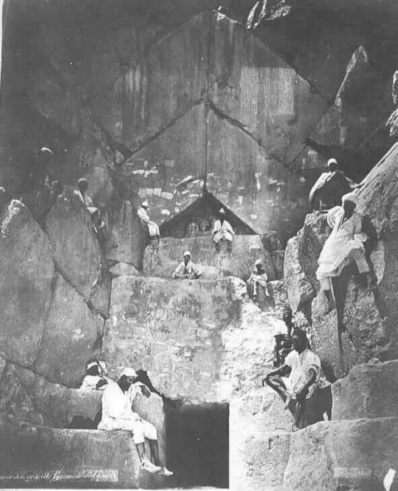 People standing and sitting on the massive stones that make up the entrance to the Pyramid. Image Credit: Public Domain.