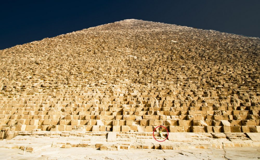 A view of the massive stones that make up the core of the Great Pyramid of Giza. Notices the person sitting on one of the stones. Shutterstock.