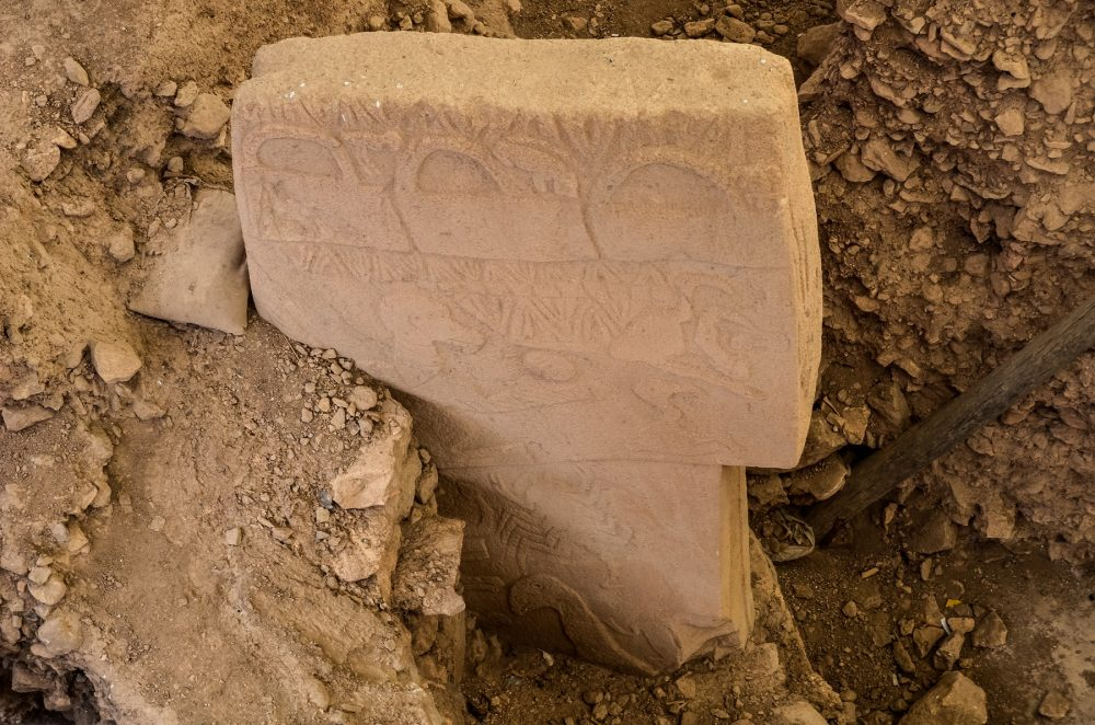An image of a half-buried stone pillar at Gobekli Tepe. Shutterstock.