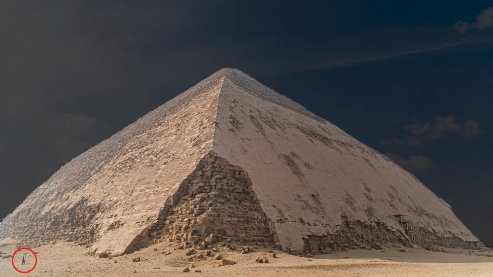 An image of the Bent Pyramid at Dahshur, and people circled in red standing next to the pyramid. Shutterstock