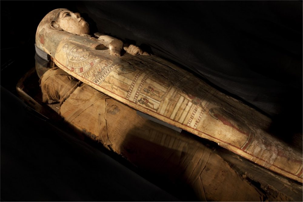 An image showing the mummified remains of Ta-Kr--Hb and her sarcophagus. Image Credit: Perth Museum.