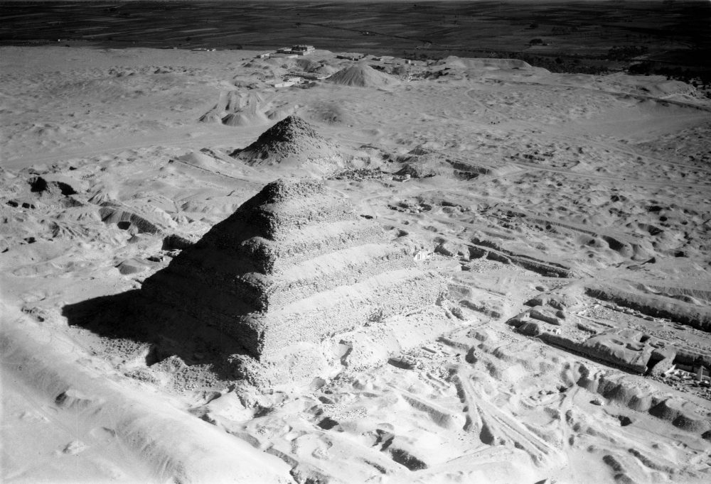 This images shows an aerial view of the Step Pyramid of Djoser. The photograph was taken on January 24, 1938. This great pyramid of six giant steps was the first of these structures. It was built by Imhotep. The pyramid was erected in the desert, and in the background the line of the Nile irrigation is seen. Image Credit: UMW Libraries.
