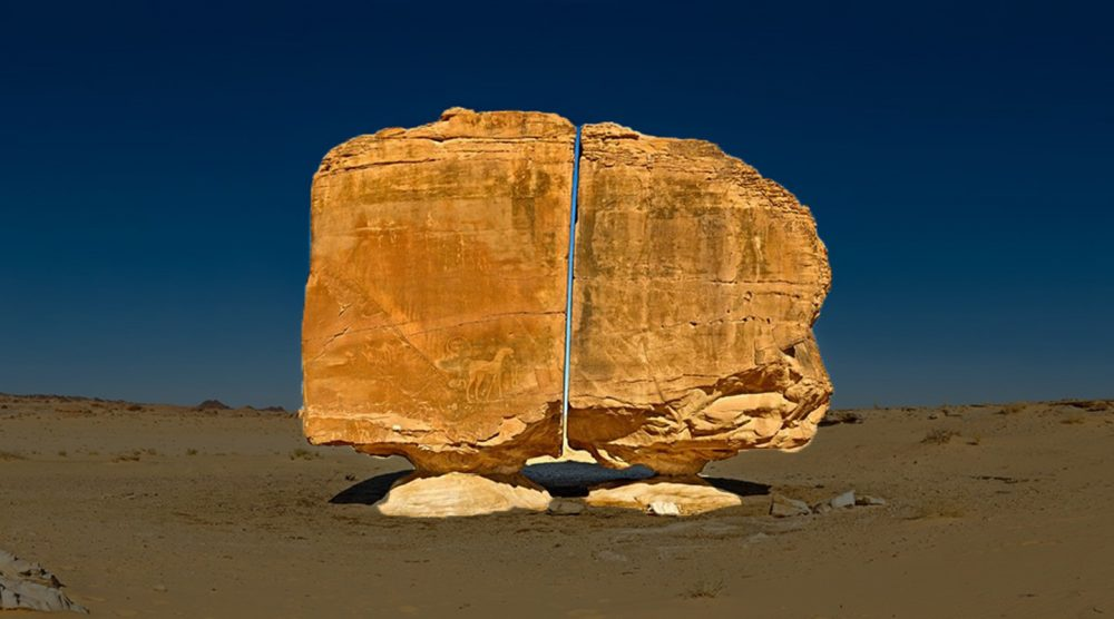 A unique view of the Al Naslaa Rock formation that appears to be split in half with laser like precision. Shutterstock.