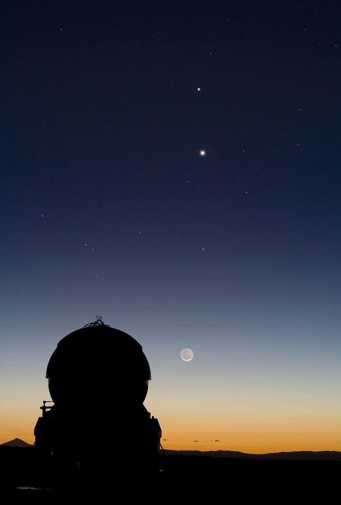 A conjunction of Mercury and Venus appears above the Moon, as viewed from the Paranal Observatory in northern Chile. Image Credit: Wikimedia Commons.