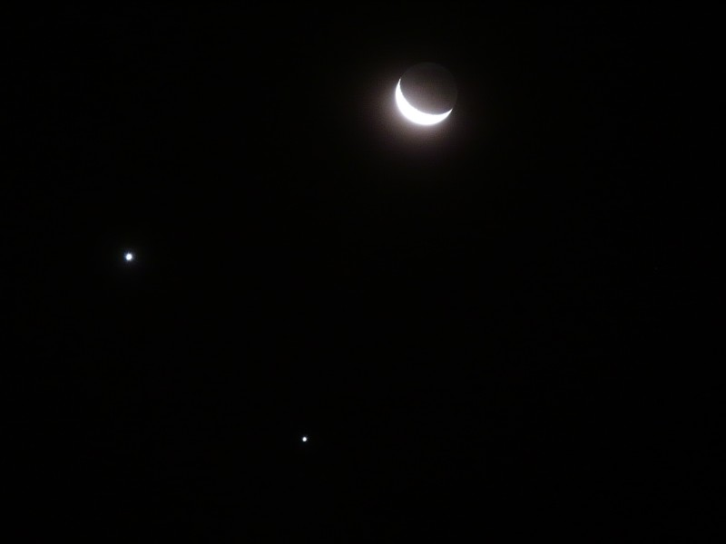 An image of a cosmic conjunction of Venus (left) and Jupiter (bottom), with the nearby crescent Moon, seen from São Paulo, Brazil, on 1 December 2008. Image Credit: Wikimedia Commons.