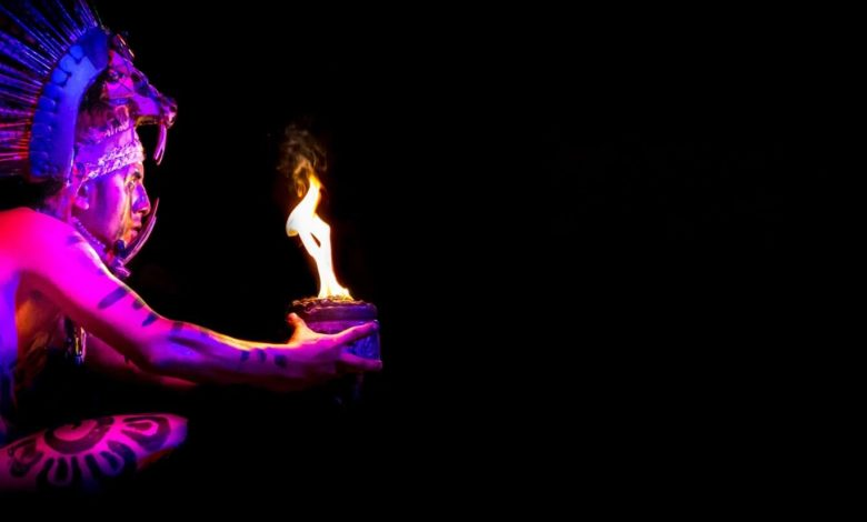An image showing a man wearing a Maya costume holding a bowl lit on fire. Jumpstory.
