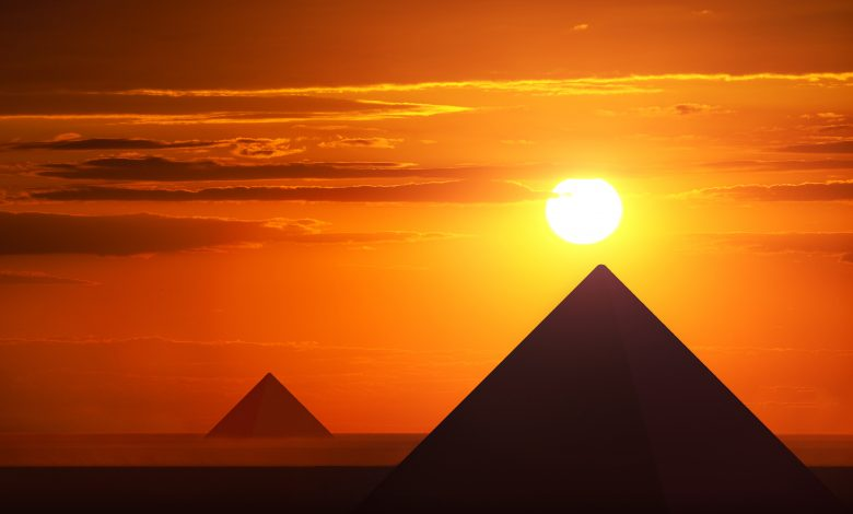 An image of the Egyptian pyramids at Giza and the sun just above them. Shutterstock.
