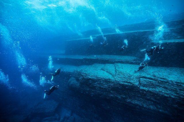 Divers exploring the Yonaguni monument near the base level.