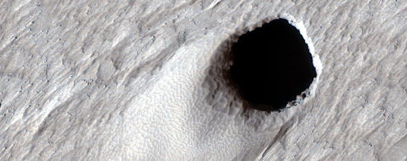 This image taken by the HiRISE camera aboard the MRO shows a massive lava tube leading towards the interior of Mars. Image Credit: NASA/JPL/UArizona.