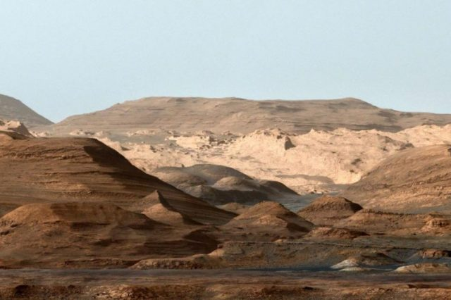 False-color image of Mount Sharp from inside the Gale Crater showing the everchanging planetary environment. Note that the sky is not blue on Mars but it was done deliberately to enhance the researchers' ability to distinguish the different stratification layers. Credit: NASA/JPL