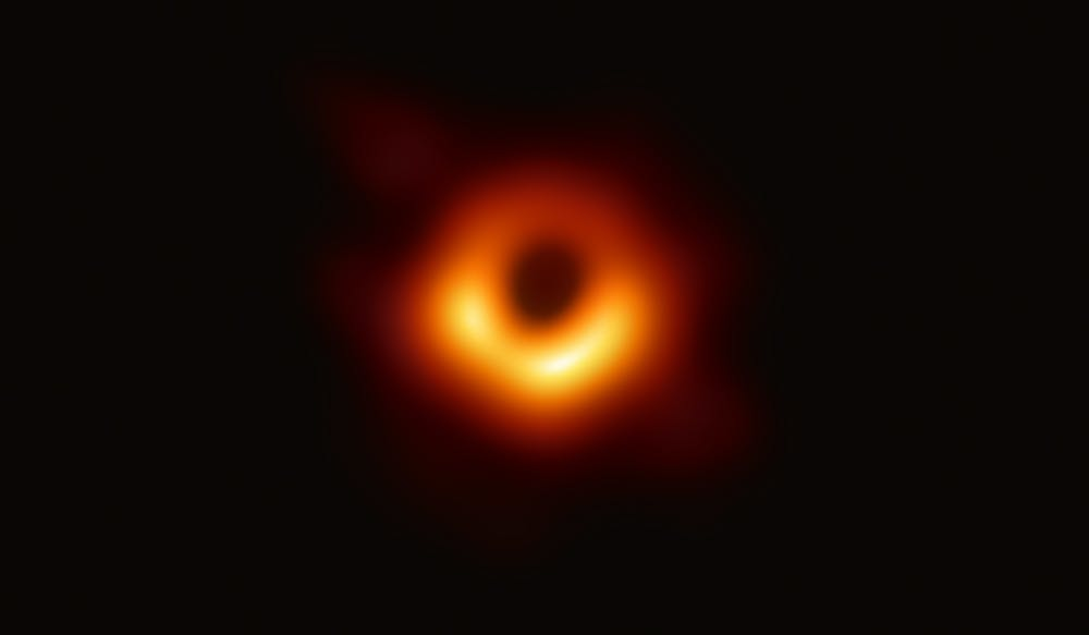 A photograph of a black hole at the center of galaxy M87. The black hole is outlined by emission from hot gas swirling around it under the influence of strong gravity near its event horizon.