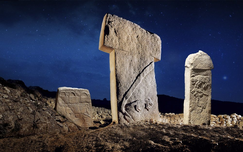 "One of the famous T-shaped pillars of Gobekli Tepe between two other curious pillars with illustrations. On the left one, you see the famous ""handbag of the Gods"", an image seen in many ancient sites around the world. Credit: Gulcan Acar"