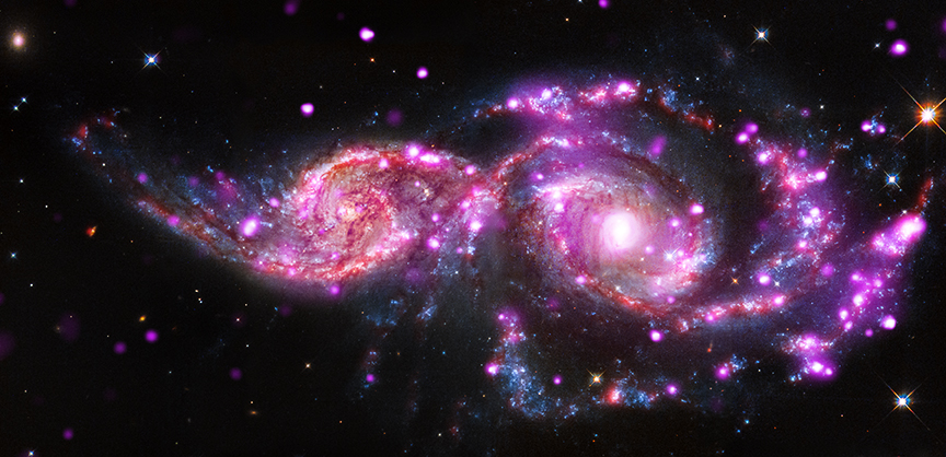 Composite image of galaxies NGC 2207 and IC 2163 which are in the process of merging. The image was made with X-Ray data from Chandra and infrared and optical data from Hubble and Spitzer. Credit: X-ray: NASA/CXC/SAO/S.Mineo et al, Optical: NASA/STScI, Infrared: NASA/JPL-Caltech