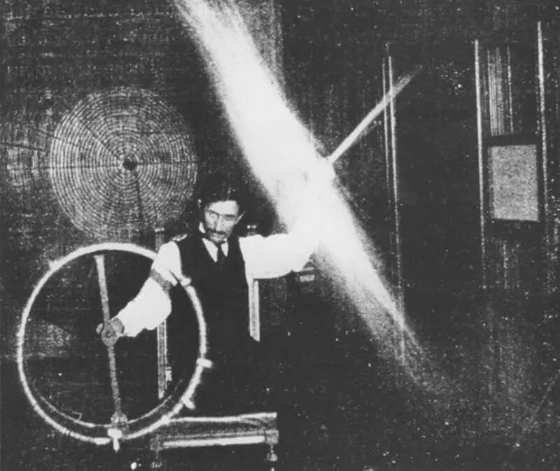 Photograph of Nikola Tesla in 1899 showing him experimenting with currents of High Voltage and High Frequency. Credit: Wikimedia Commons