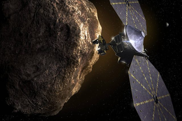 Artist's impression of the Lucy as it passes near a Trojan asteroid with Jupiter in the distant background. Credit: Southwest Research Institute