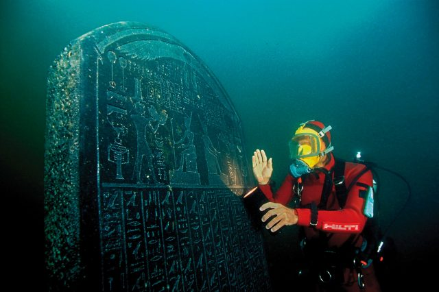 Underwater archaeologist imaged next to a massive slab in Heracleion. Credit: Wikimedia Commons