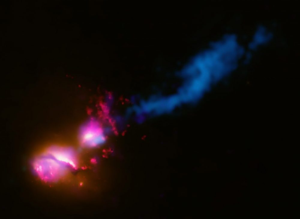 Composite image of radio galaxy 3C321 with X-ray data (colored purple), optical and UV (red and orange) and radio emissions (blue). Credit: X-ray: NASA/CXC/CfA/D.Evans et al.; Optical/UV: NASA/STScI; Radio: NSF/VLA/CfA/D.Evans et al., STFC/JBO/MERLIN