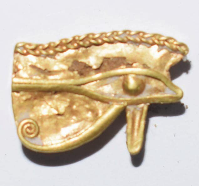 """A golden amulet with the shape of the """"Eye of Horus"""". Credit: Ministry of Antiquities / Facebook"""