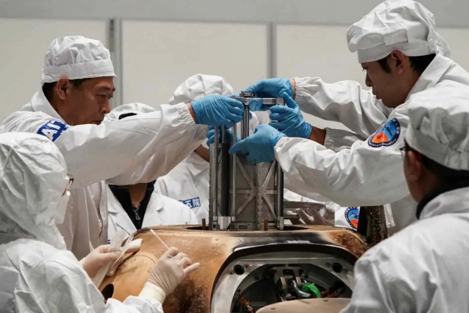 Experts remove a container with lunar samples from the landing capsule. Credit: Fu Yifei / Science and Technology Daily.